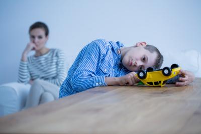 sad boy playing toy car