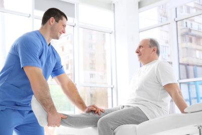 therapist helping elder man to stretch